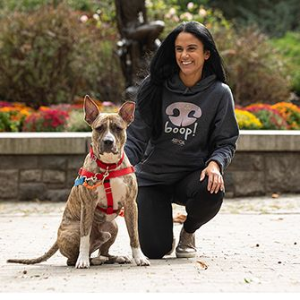 a woman and dog outside with an aspca hoodie