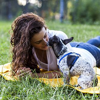 a dog licking a woman on the nose in a park