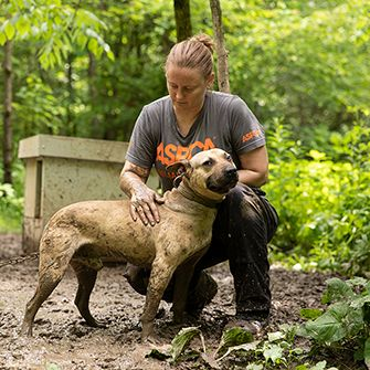 an aspca responder with a dog chained in mud