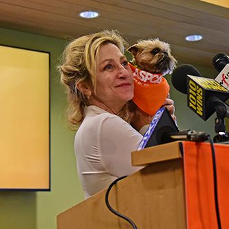 Edie Falco holding a small dog at a podium