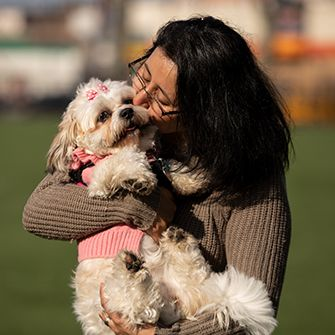 a woman kissing and hugging a dog