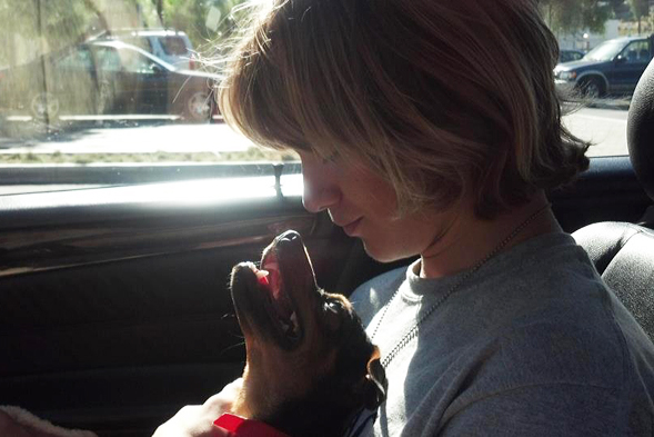 Young man with blonde hair holds puppy in car