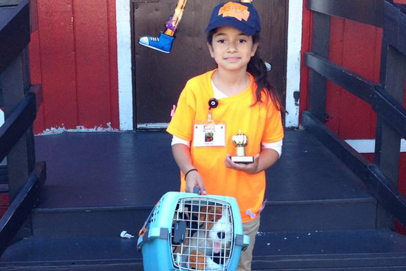 Young girl wearing ASPCA Halloween Costume and holding prize